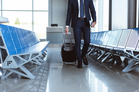 Businessman with travel bag walking along departure lounge in airport