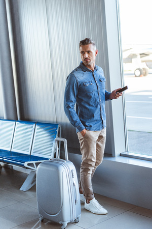 Man in a blue shirt keeping phone in the hand and looking at something in the airport