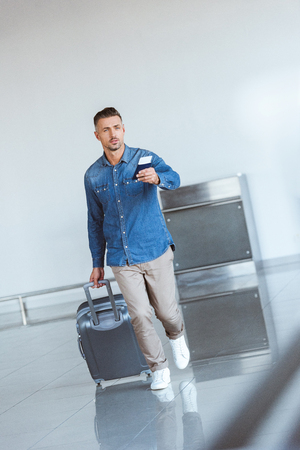 Handsome tourist with silver travel bag in the airport