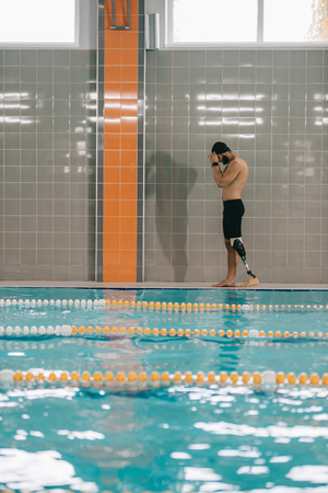 Handsome young sportsman with artificial leg walking by poolside at indoor swimming pool