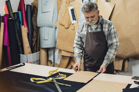 Mature leather handbag craftsman in apron working at studio