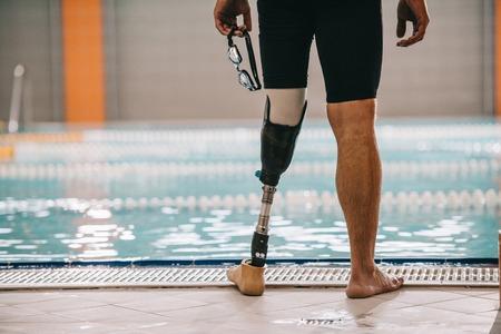 Przycięte zdjęcie pływaka ze sztuczną nogą stojącego przed krytym basenem i trzymającego okulary pływackie Zdjęcie Seryjne