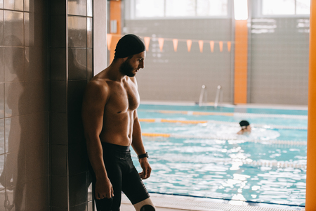 Handsome swimmer with artificial leg standing at poolside of indoor swimming pool