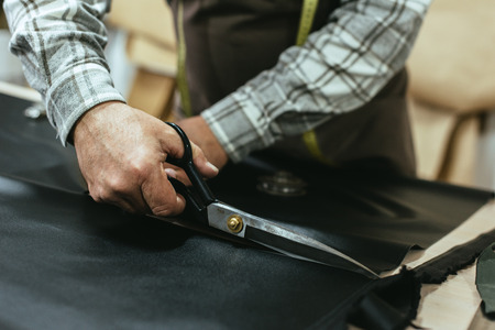 Partial view of male handbag craftsman cutting leather by scissors at studio