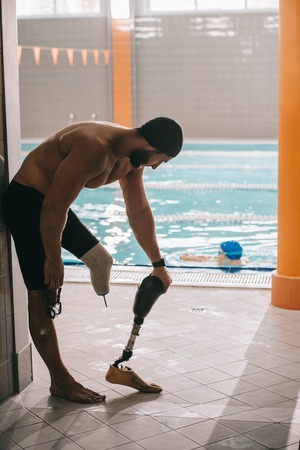 Athletic young swimmer standing at poolside of indoor swimming pool and taking off artificial leg