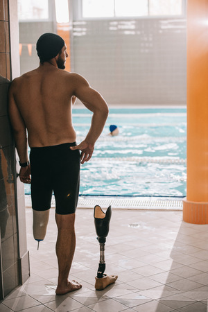 Rear view of swimmer standing at poolside of indoor swimming pool and taking off artificial leg Banco de Imagens