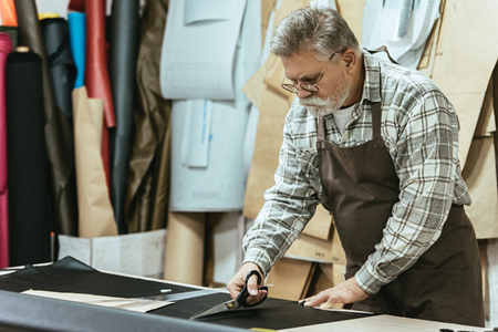 Mature male handbag craftsman in apron and eyeglasses cutting leather by scissors at workshop