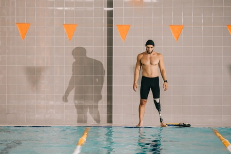 Muscular young sportsman with artificial leg looking at indoor swimming pool Stock Photo