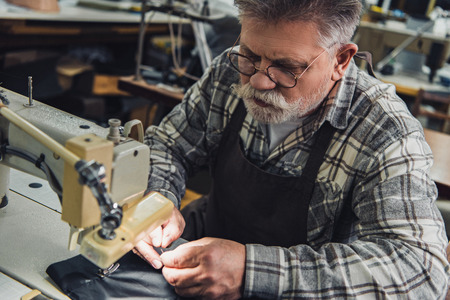 High angle view of male handbag craftsman working on sewing machine at studio Stock Photo