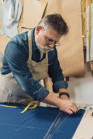 Concentrated male middle aged craftsman in apron making measurements on fabric at workshop