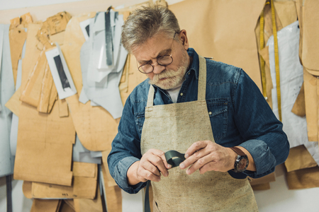 Concentrated middle aged male handbag craftsman in apron and eyeglasses working with fabric at studio