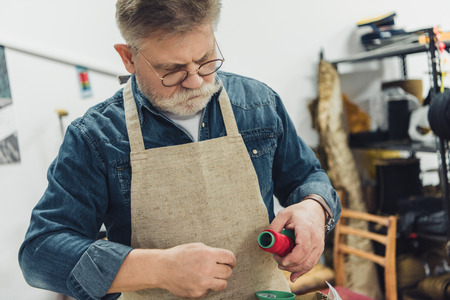 Mature male craftsman in apron working with strings at studio