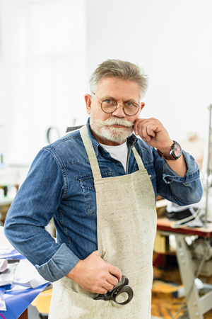 Middle aged male craftsman in apron looking at camera and posing at workshop