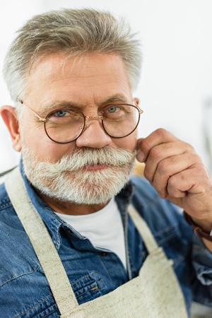 Alegre artesano masculino de mediana edad en delantal mirando a la cámara en el estudio Foto de archivo