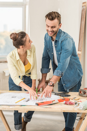Happy young couple discussing blueprint during renovation Stockfoto