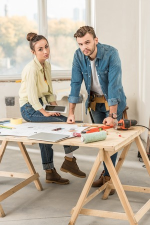 Upset young couple leaning at table with tools and looking at camera during renovation Stock Photo