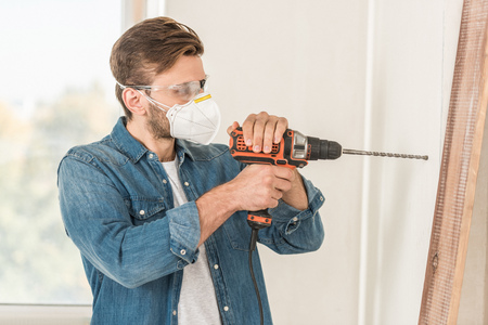 Young man in protective mask and goggles using electric drill during house repair Stockfoto
