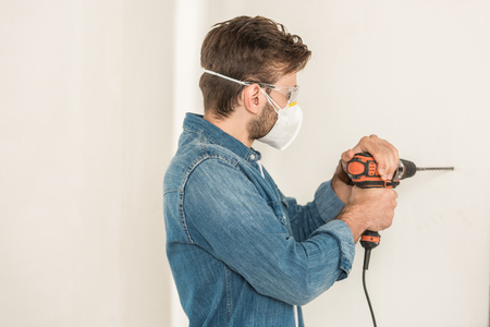 Young man in protective work wear using electric drill at wall during house repair Stock Photo