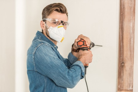 Young man in protective work wear using electric drill and looking at camera during house repair