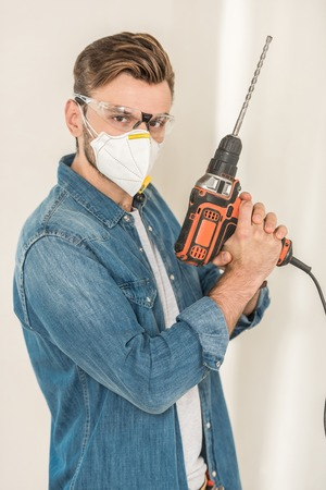 Young man in protective goggles and mask holding electric drill and looking at camera