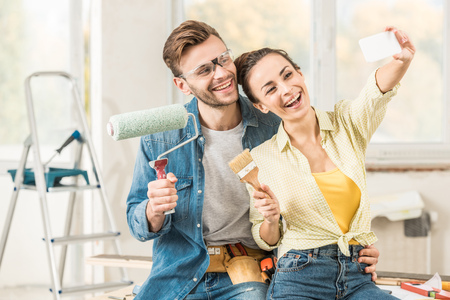 Happy young couple holding tools and taking selfie with smartphone while making repairment