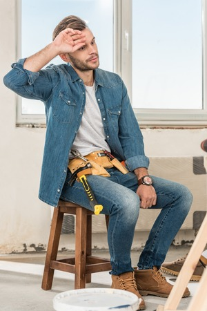 Tired young man with toolbelt sitting on chair during house repair