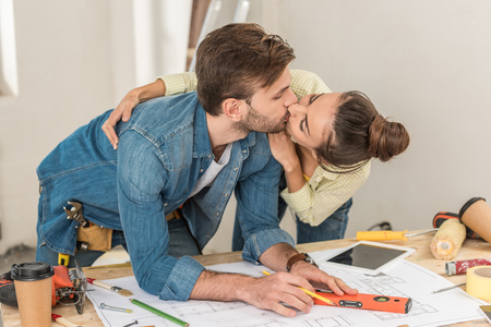 Young couple kissing while man marking blueprint with level tool Stock Photo