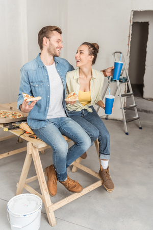 Happy young couple with pizza and paper cups sitting together and smiling each other during repairment