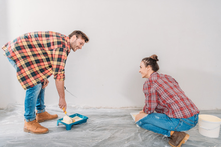 Happy young couple painting wall with paint rollers and smiling each other