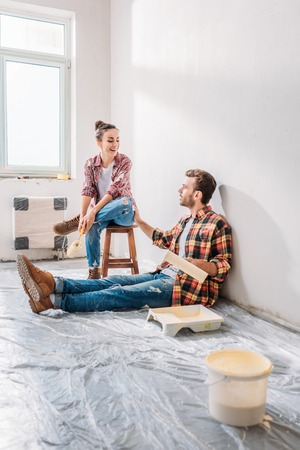 Smiling young couple holding paint rollers and talking in new apartment Imagens