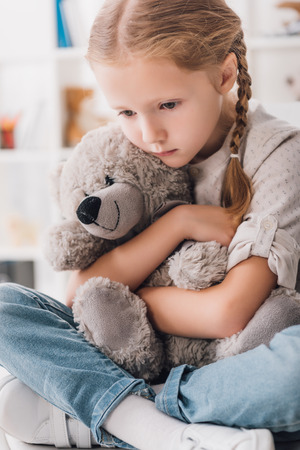 Close-up portrait of depressed little child embracing her teddy bear Stock fotó