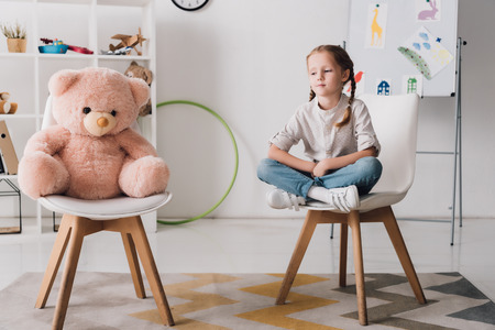 Lonely little child sitting on chair near pink teddy bear