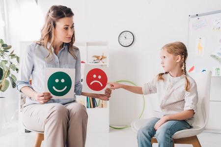 Psicólogo de adultos que muestra emociones felices y tristes enfrenta tarjetas al niño Foto de archivo