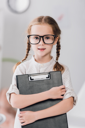 Smiling little child in eyeglasses with clipboard looking at camera
