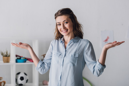 Smiling adult woman shrugging shoulders and looking at camera Stock Photo