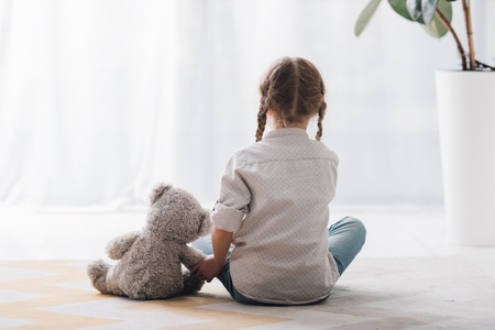 Rear view of little child sitting on floor with her teddy bear toy