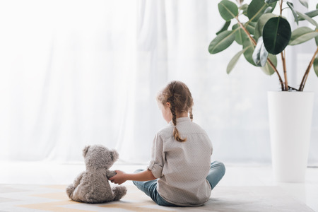 Rear view of little child sitting on floor in front of curtains with teddy bear