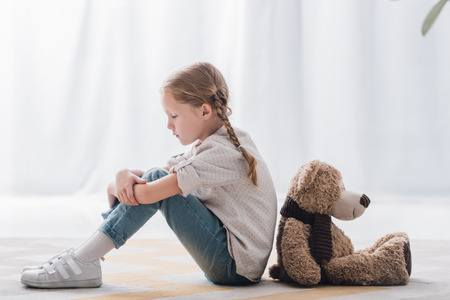 Side view of sad little child sitting on floor back to back with teddy bear