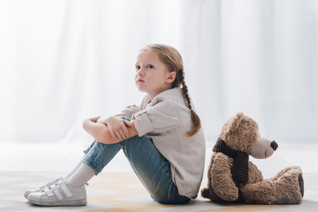 Side view of depressed little child sitting on floor back to back with teddy bear