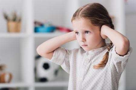 Close-up retrato de niño cubriendo las orejas con las manos y mirando a otro lado