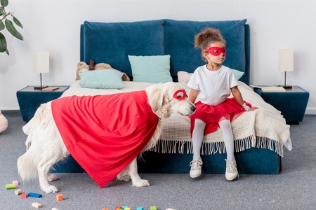 Cute little African american kid with dog in superhero costumes in bedroom Stock Photo