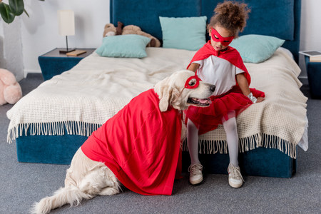 Adorable little African american kid playing with dog in superhero costumes in bedroom