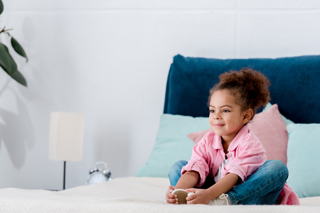 Smiling African american kid siting on the bed clasping her legs Stock Photo