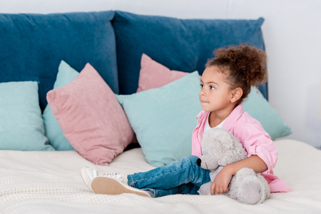 Adorable African american child sitting on the bed with her toy