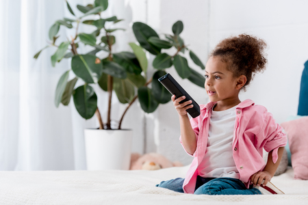 Adorable African american child sitting on the bed and and switching channels on tv Stock Photo