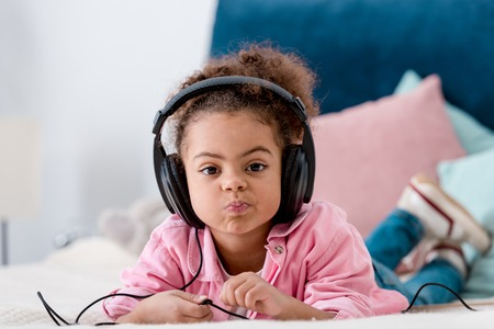 African american kid with funny face lying on the bed in headphones