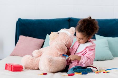 Adorable African american kid examining teddy bear