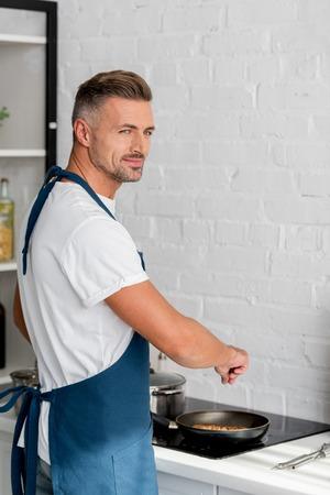 Handsome man in apron salting steak on pan 版權商用圖片