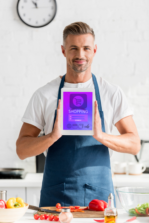 Man holding digital tablet with online shopping illustration at kitchen