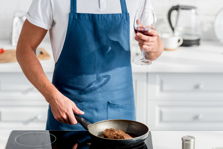 Cropped view of man with glass of wine cooking steak on pan